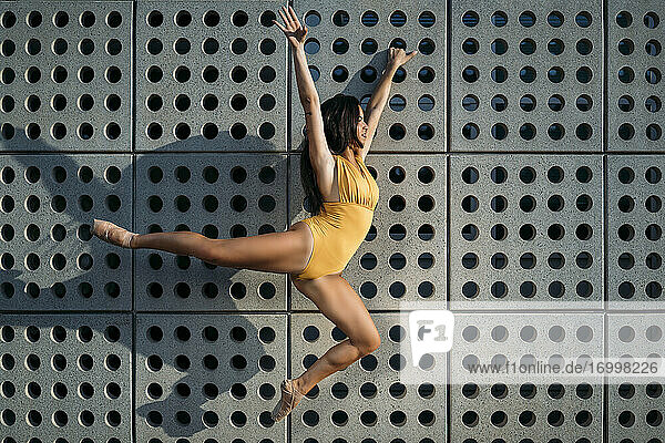 Ballerina dancing in front of a wall