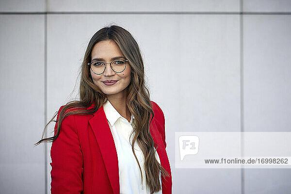 Businesswoman wearing eyeglasses standing against wall