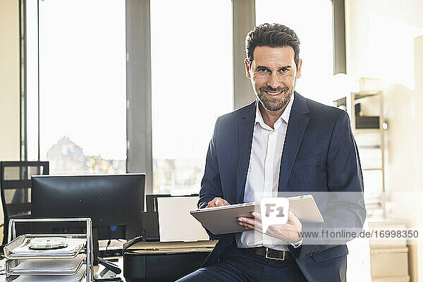 Smiling businessman using digital tablet while sitting at office