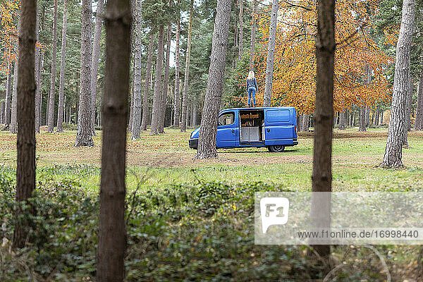 Mid adult woman standing on rooftop of camper van at Cannock Chase