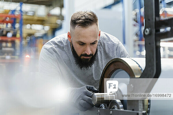 Mid adult male technician concentrating while analyzing machine part at factory