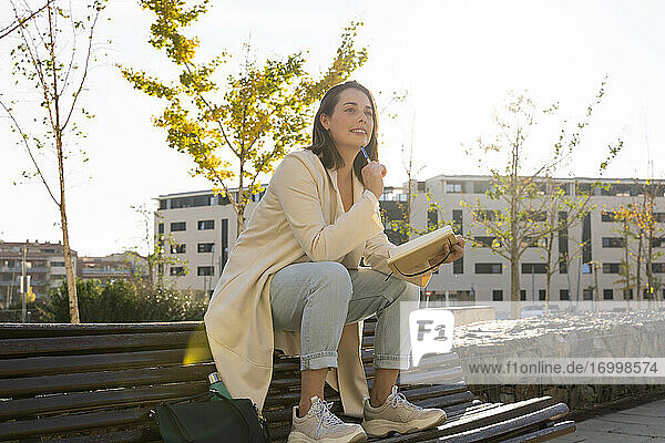 Thoughtful businesswoman sitting on bench with book
