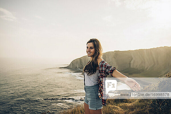 Smiling woman with arms outstretched looking at view while standing against sky