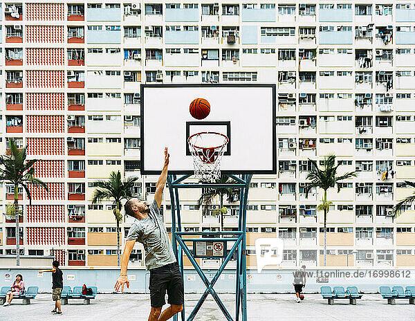 China  Hong Kong  Kowloon  man playing basketball  public housing in the background
