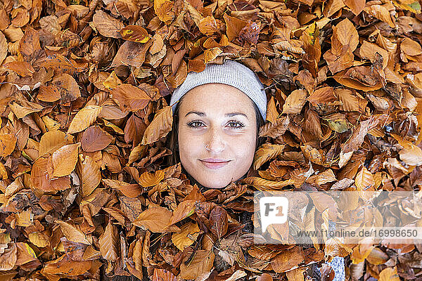 Beautiful woman's face surrounded by autumn leaves in Cannock Chase woodland