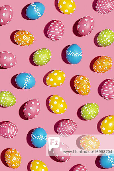 Colorful decorated Easter eggs on pink background