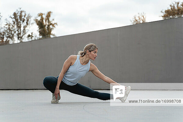Woman stretching leg while doing warm up exercise against wall