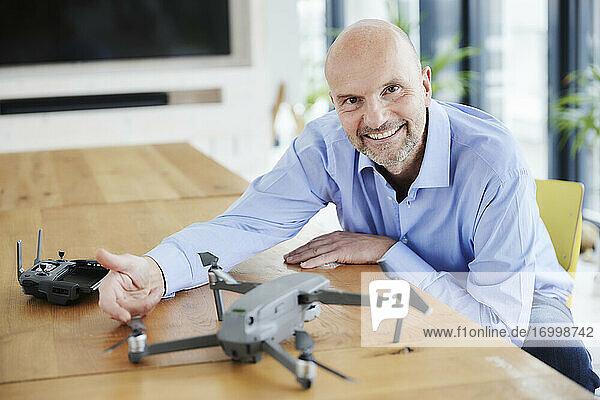 Smiling man checking quadcopter