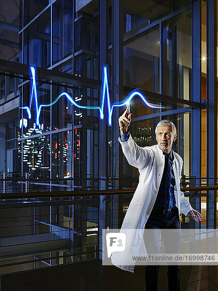 Male cardiologist examining pulse trace with light painting at hospital