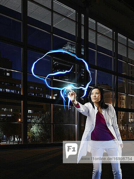 Älterer weiblicher Neurologe  der das Gehirn mit Lichtmalerei im Krankenhaus analysiert Älterer weiblicher Neurologe, der das Gehirn mit Lichtmalerei im Krankenhaus analysiert