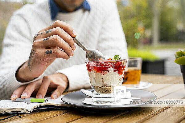 Man scooping dessert with spoon at cafe