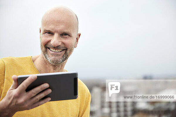 Mature man smiling while using digital tablet on rooftop