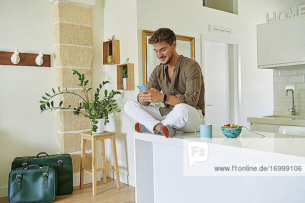 Lächelnder Mann  der eine Textnachricht auf seinem Smartphone sendet  während er über dem Tresen in der Küche zu Hause sitzt Lächelnder Mann, der eine Textnachricht auf seinem Smartphone sendet, während er über dem Tresen in der Küche zu Hause sitzt
