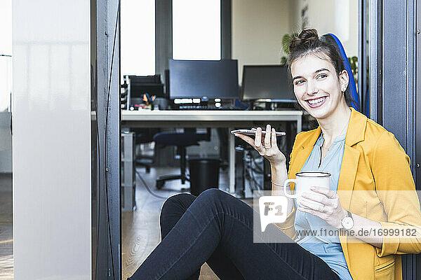 Geschäftsfrau mit Kaffeetasse  die mit ihrem Handy telefoniert  während sie am Eingang eines Büros sitzt Geschäftsfrau mit Kaffeetasse, die mit ihrem Handy telefoniert, während sie am Eingang eines Büros sitzt