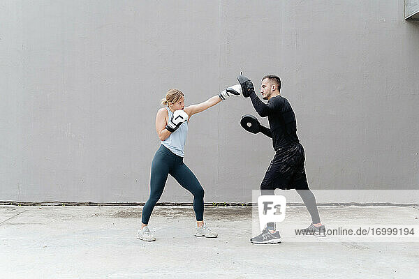 Sportswoman boxing with man while standing against wall