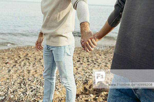 Junges Paar hält sich an den Händen  während es am Strand im Sand steht Junges Paar hält sich an den Händen, während es am Strand im Sand steht