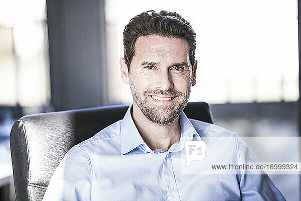 Mature businessman smiling while sitting on chair at office