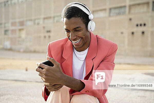 Happy man wearing headphones using mobile phone while sitting outdoors
