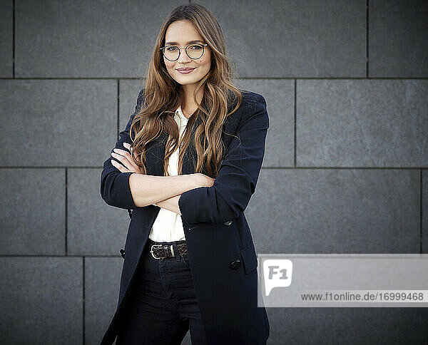 Confident business professional with arm crossed standing against concrete brick wall