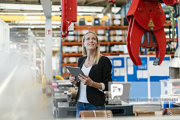 Lächelnde Geschäftsfrau  die eine Klaue untersucht und ein digitales Tablet in einer Fabrik hält