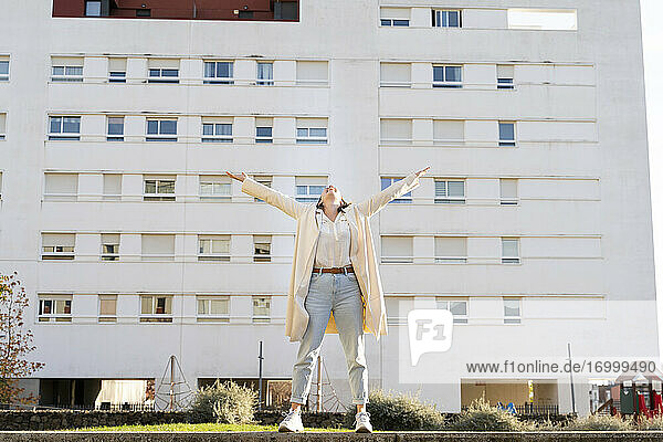 Female entrepreneur with arms outstretched standing against building in garden