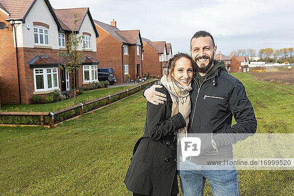 Lächelnder Mann  der seine Freundin umarmt  während er vor seinem neuen Haus steht