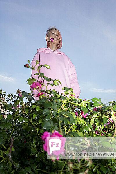 Junge Frau mit rosa Haaren und rosa Kapuzenshirt in der Nähe eines Rosenstrauchs Junge Frau mit rosa Haaren und rosa Kapuzenshirt in der Nähe eines Rosenstrauchs