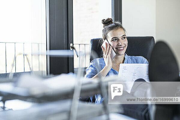 Unternehmerin lächelt  während sie im Büro mit dem Handy telefoniert Unternehmerin lächelt, während sie im Büro mit dem Handy telefoniert