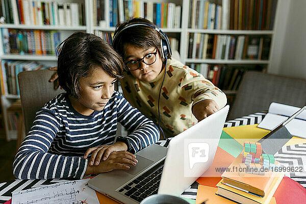 Jungen schauen beim E-Learning im Wohnzimmer auf den Laptop Jungen schauen beim E-Learning im Wohnzimmer auf den Laptop