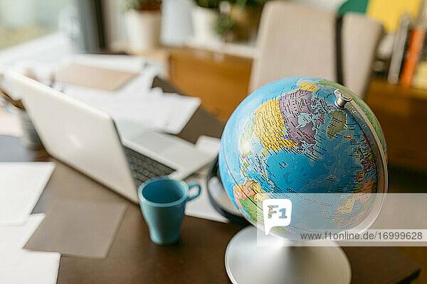 Globus mit Laptop und Tasse auf dem Tisch Globus mit Laptop und Tasse auf dem Tisch
