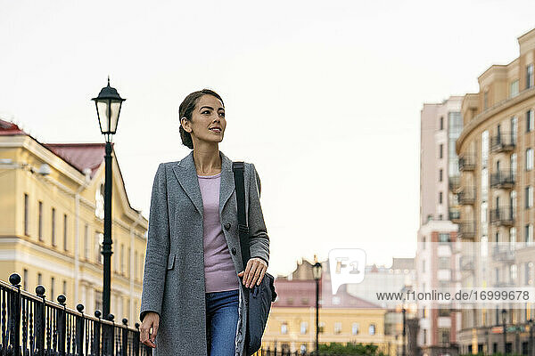 Female entrepreneur looking away while walking in city during autumn