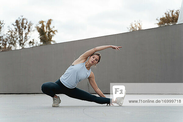 Young woman stretching legs and hands while exercising outdoors