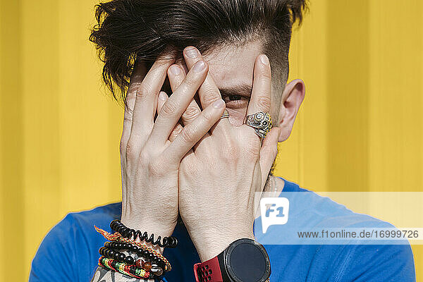 Young man standing in front of yellow wall  hiding face behind his hands