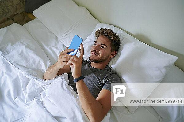 Lächelnder Mann  der ein Smartphone benutzt  während er auf dem Bett im Schlafzimmer liegt Lächelnder Mann, der ein Smartphone benutzt, während er auf dem Bett im Schlafzimmer liegt