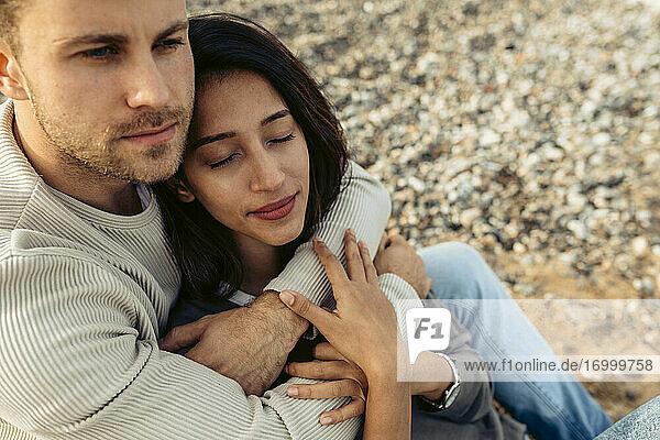 Junger Mann  der eine Frau umarmt und dabei auf den Strand schaut Junger Mann, der eine Frau umarmt und dabei auf den Strand schaut