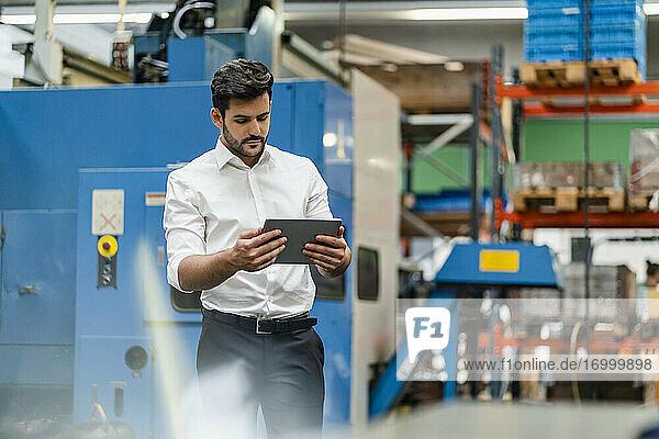 Geschäftsmann  der ein digitales Tablet benutzt  während er in einer Fabrik steht