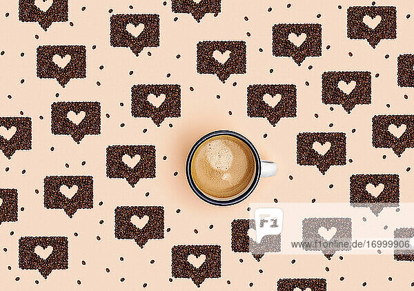 Pattern of mug of coffee surrounded by roasted coffee beans arranged into shapes of online chat bubbles