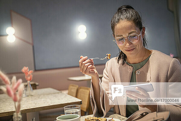 Smiling businesswoman having food while using mobile phone sitting at modern cafe