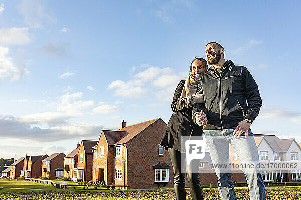 Happy couple looking away while standing outside newly built houses against sky