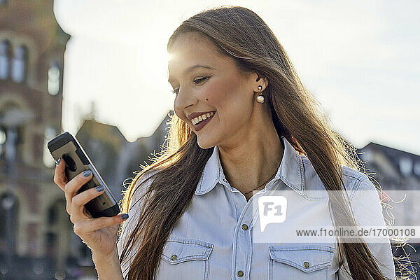 Happy businesswoman using mobile phone while standing in city