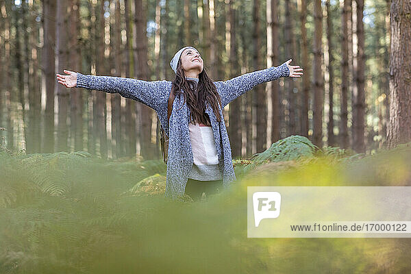 Beautiful female hiker with arms outstretched standing in Cannock Chase woodland during winter