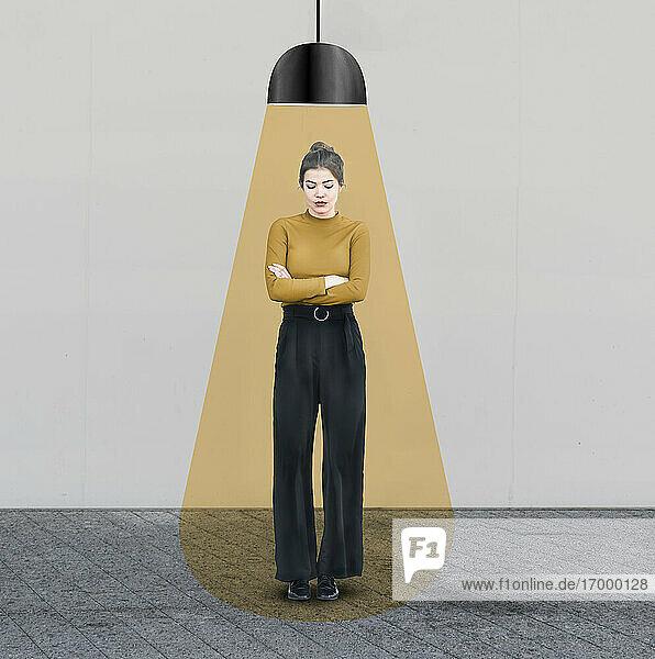 Traurige Frau mit verschränkten Armen steht unter beleuchtetem Licht an der Wand Traurige Frau mit verschränkten Armen steht unter beleuchtetem Licht an der Wand