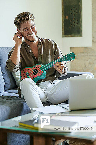 Smiling man learning ukulele through online tutorial on laptop at home