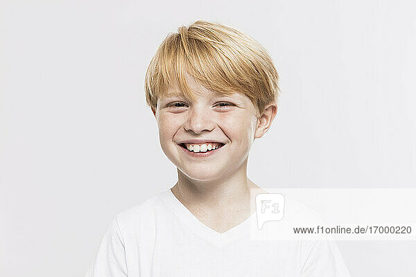 Cheerful cute boy with blond hair against white background