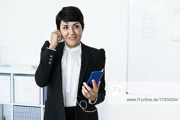 Portrait of businesswoman using smart phone with headphones
