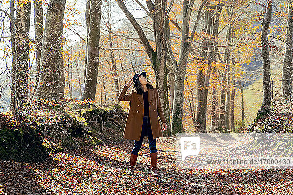 Woman wearing hat and jacket looking up while standing on footpath at forest