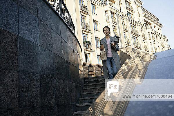 Unternehmerin steigt in der Stadt die Treppe hinunter Unternehmerin steigt in der Stadt die Treppe hinunter