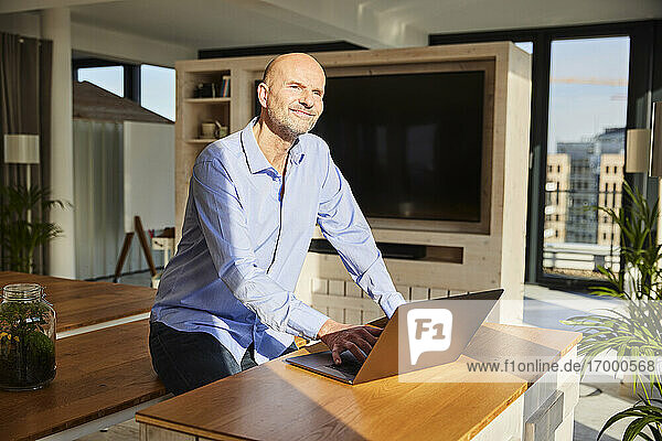 Smiling businessman looking away while using laptop sitting at home