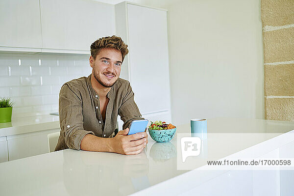 Junger Mann mit Smartphone an der Theke in der Küche zu Hause Junger Mann mit Smartphone an der Theke in der Küche zu Hause