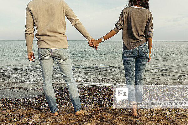 Young couple holding hands while standing on sand at beach